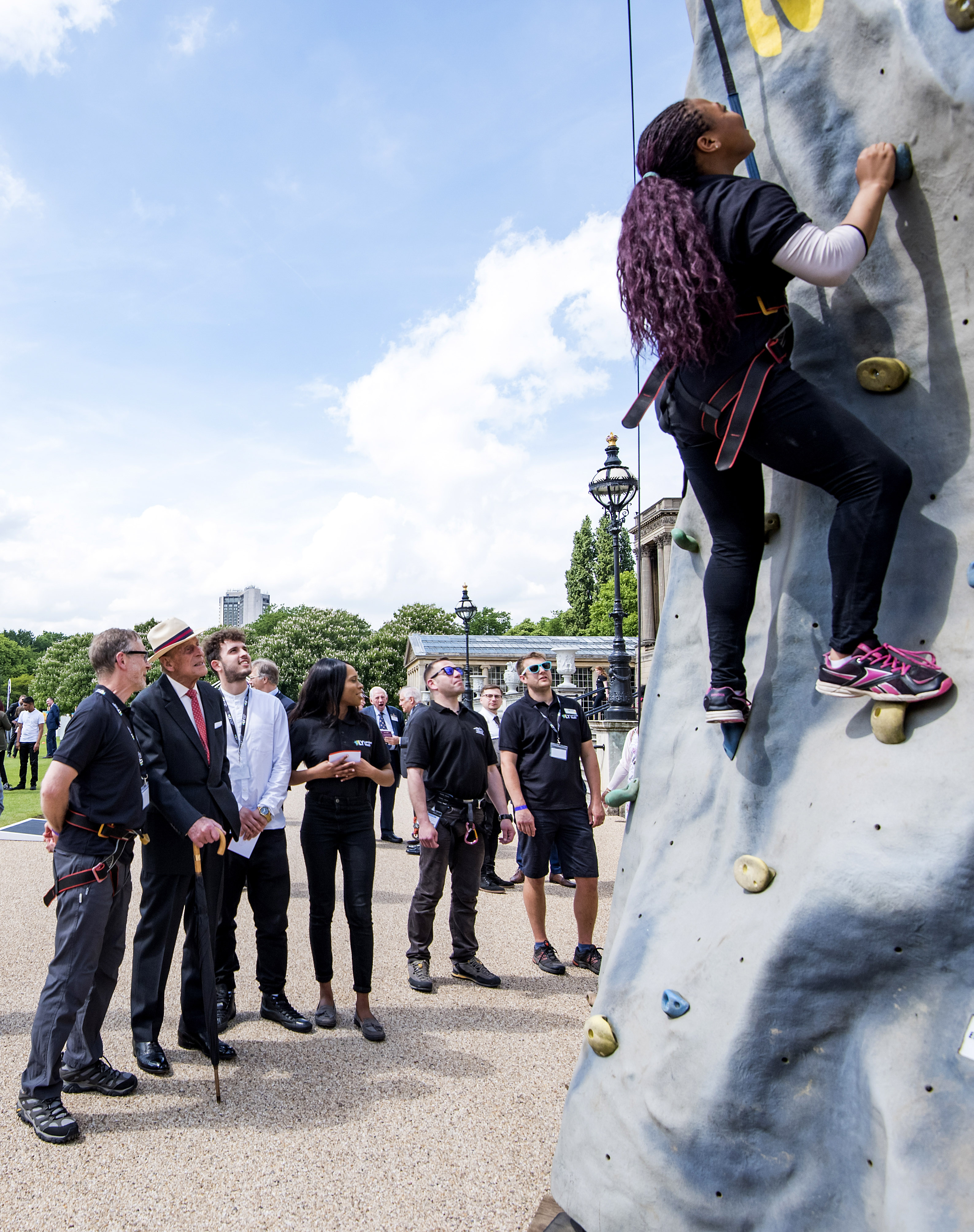 Prince Philip stands by a rock climbing wall