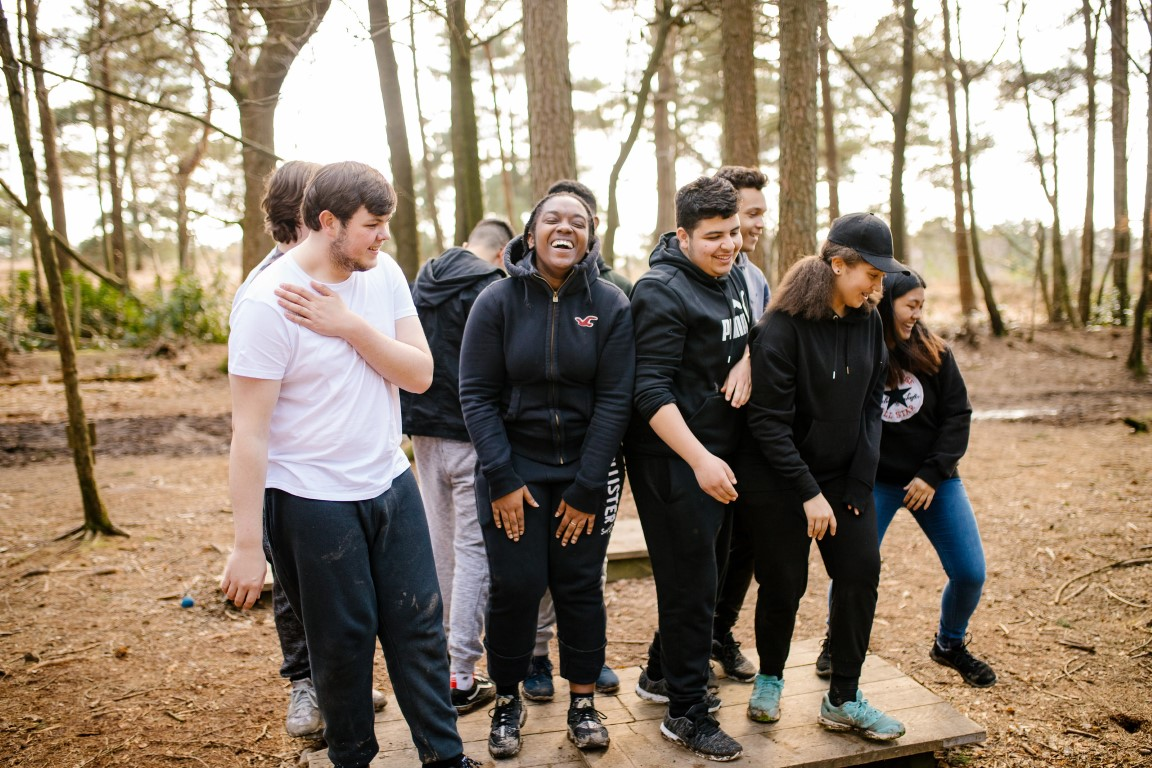 group of young people outdoors, they are standing together and smiling and laughing